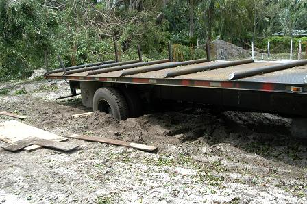 An 18 wheeler flatbed truck gets stuck in sand blown onto the roadway.