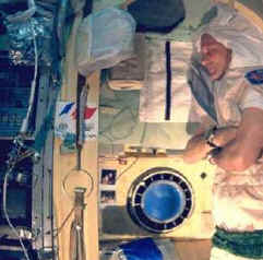 A member of the MIR Space Station crew catches some sleep next to the window.